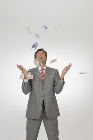 Businessman Throwing Euro Banknotes In The Air,Looking Up,Portrait LANG_EVOIMAGES