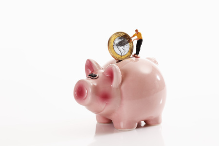 Figurine With 1 Euro Coin On Piggy Bank