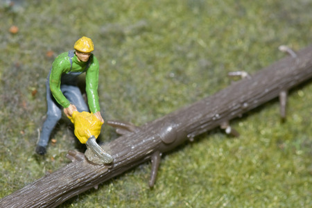 Figurine Of Lumberman Cutting Tree Trunk With Electric Saw