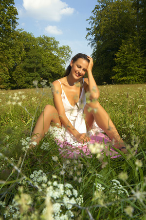 Germany,Bavaria,Woman Sitting In A Meadow,Smiling