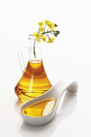 Rapeseed Oil In Jar And Ladle With Rape Blossom On White Background
