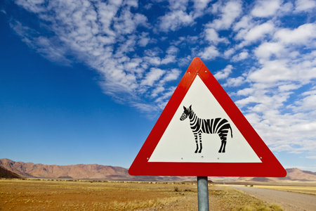 Africa,Namibia,Namib Desert,Close Up Of Animal Crossing Sign Gravelroad Through Namib Rand