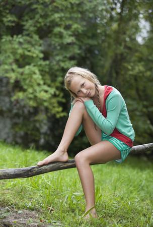 Austria,Mondsee,Girl (12-13 Years) Sitting On Branch,Portrait LANG_EVOIMAGES