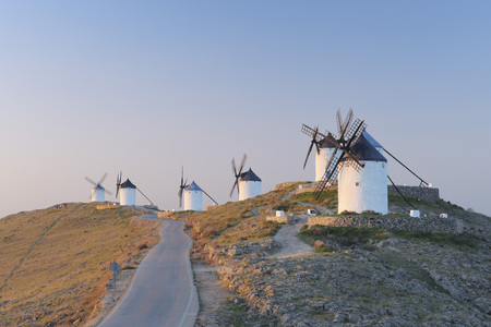 Spain,Toledo Province,Castile-La Mancha,Row Of Windmills With Rural Road At Sunrise LANG_EVOIMAGES