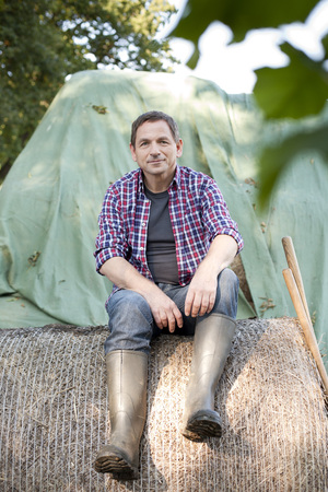 Germany,Saxony,Mature Man Sitting On Hay Bale At The Farm LANG_EVOIMAGES
