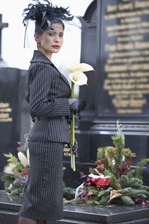Germany,Bavaria,Young Woman With Flower At Graveyard