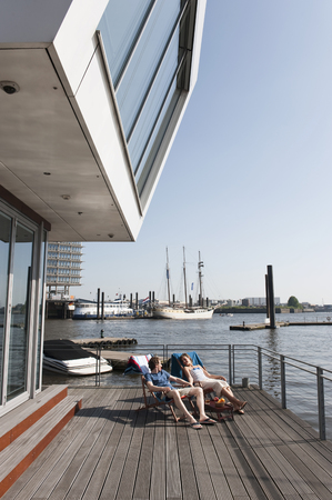 Germany,Hamburg,Couple Relaxing In Deck Chair On Floating Home