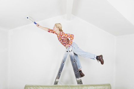 Germany,Cologne,Mature Woman Balancing On Ladder During Painting Gable Roof