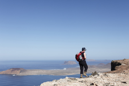 Spain,Canary Islands,Lanzarote,Risco De Famara,Mature Woman Walking On Cliff,Island La Graciosa In Background LANG_EVOIMAGES