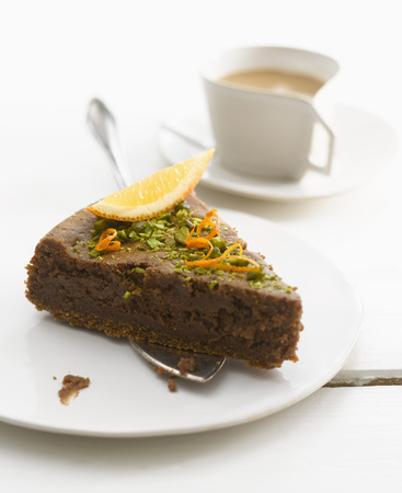 Plate Of Brownie Cake Garnished With Orange Slice And Pistachios,Close-Up