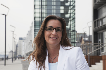 Germany,Cologne,Businesswoman With Spectacles Next To Rhine River And Crane House In Background,Smiling,Portrait