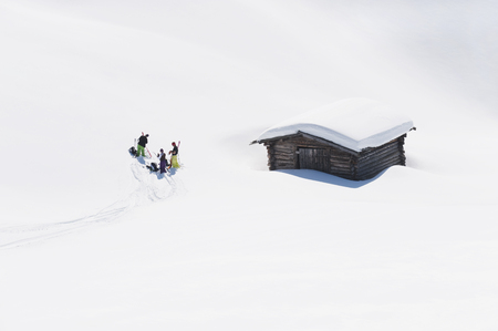 Italy,Trentino-Alto Adige,Alto Adige,Bolzano,Seiser Alm,Group Of People Near House On Ski Tour