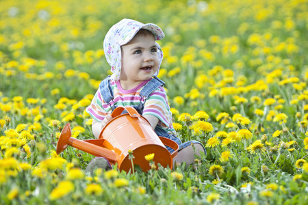 Germany,Bavaria,Baby Girl Holding Watering Can In Flower Field,Smiling