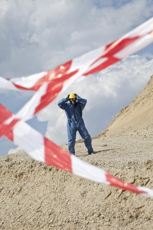 Germany,Bavaria,Man In Protective Wear On Sand Dune And Cordon Tape In Foreground LANG_EVOIMAGES