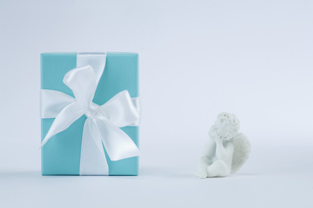 Gift Box With Putto On Blue Background