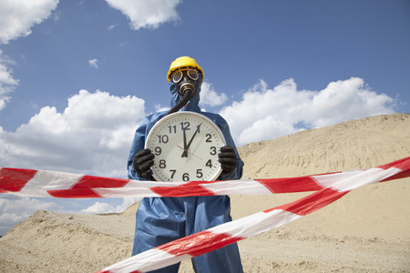 Germany,Bavaria,Man In Protective Wear With Clock Near Sand Dune And Cordon Tape In Foreground LANG_EVOIMAGES