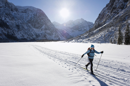 Germany,Bavaria,Senior Woman Doing Cross-Country Skiing With Karwendal Mountains In Background LANG_EVOIMAGES