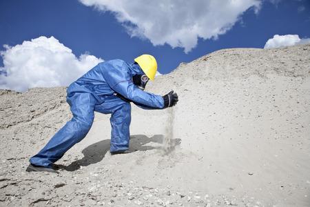 Germany,Bavaria,Man In Protective Wear Spilling Sand On Sand Dune LANG_EVOIMAGES