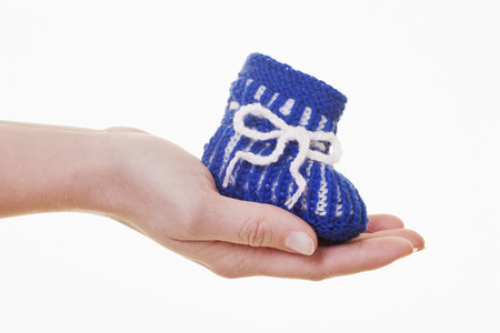 Hand Of Woman Holding Woollen Baby Shoe Against White Background,Close Up
