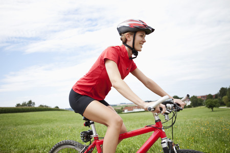Germany,Bavaria,Young Woman Riding Mountain Bike LANG_EVOIMAGES