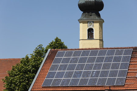 Germany,Bavaria,Upper Bavaria,Frauenried,View Of Solar Collector On Roof And Church Tower In Background