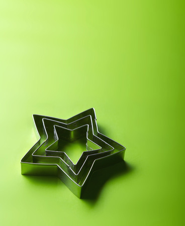 Star Shape Cookie Cutters On Green Background LANG_EVOIMAGES