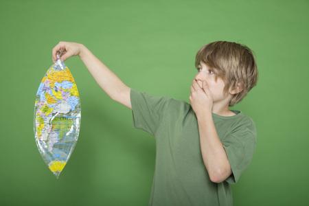 Boy Holding Deflated Air Globe Against Green Background
