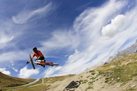 Italy,Livigno,View Of Man Jumping With Mountain Bike LANG_EVOIMAGES