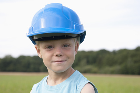 Germany,North Rhine-Westphalia,Hennef,Boy With Construction Worker Helmet Standing In Meadow,Portrait,Close Up