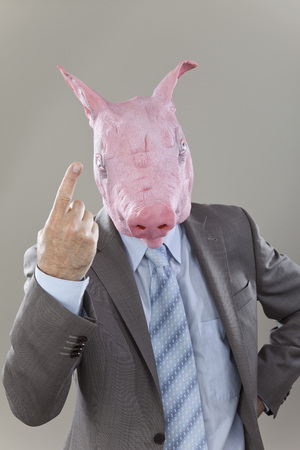 Close Up Of Businessman With Pigs Head In Office Against Grey Background