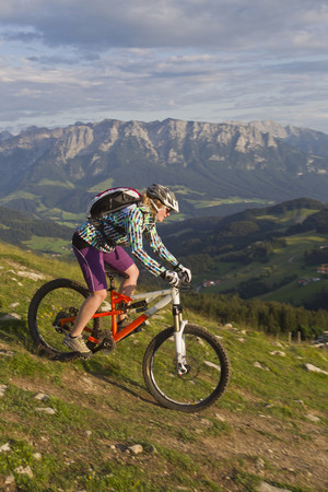 Austria,Tyrol,Spitzstein,Young Woman Mountainbiking On Slope With Kaiser Mountains In Background LANG_EVOIMAGES