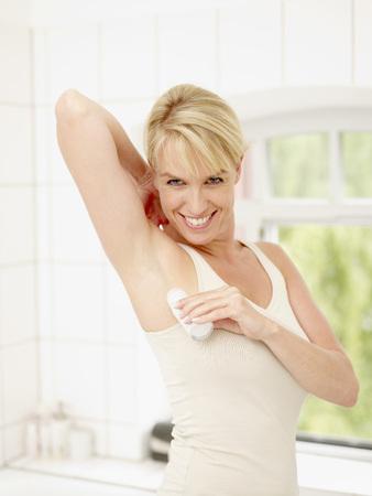 Mature Woman Putting Deodorant On Underarms,Smiling,Portrait LANG_EVOIMAGES