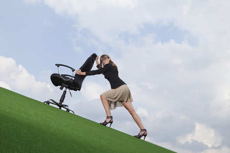 Germany,Bavaria,Munich,Businesswoman Pushing Chair On Lawn