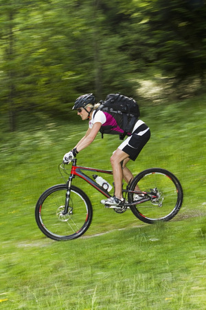 Germany,Bavaria,Schliersee,Mid Adult Woman Moutainbiking On Grass LANG_EVOIMAGES