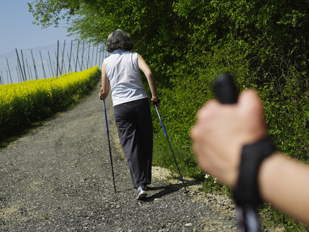 Germany,Bavaria,Mature Woman Nordic Walking With Man Holding Pole