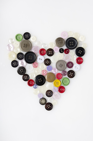 Colourful Buttons Arranged In Heart Shape On White Background