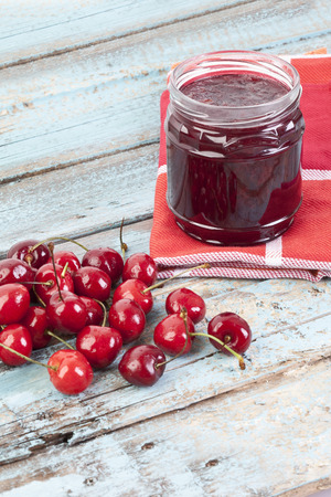 Cherries Beside Open Jar Of Cherry Jam On Wooden Table,Close Up