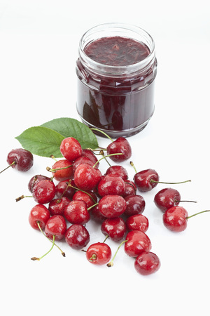 Cherries Beside Open Jar Of Cherry Jam On White Background,Close Up LANG_EVOIMAGES