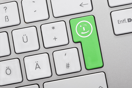 Close Up Of Computer Keys With Smiley Face Symbol On Green Key Stock