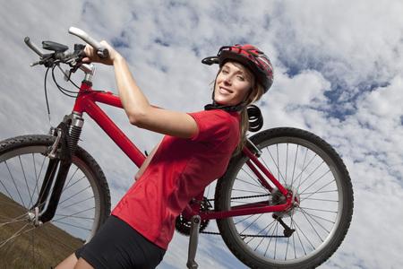 Germany,Bavaria,Young Woman Carrying Mountain Bike