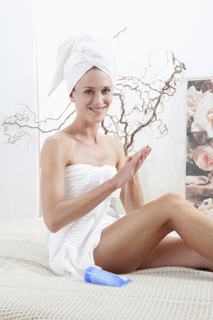 Young Woman Wrapped In Towel Rubbing Body Cream LANG_EVOIMAGES
