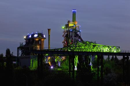 Germany,Nordrhein-Westfalen,Duisburg,Duisburg-Nord Landscape Park,View Of Illuminated Blast Furnace And Smoke Stacks Of Old Industrial Plant LANG_EVOIMAGES