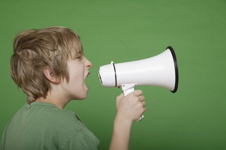 Close Up Of Boy Screaming In Megaphone Against Green Background LANG_EVOIMAGES