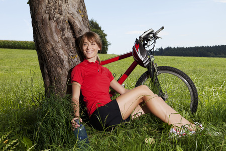 Germany,Bavaria,Young Woman Sitting Against Tree With Mountain Bike LANG_EVOIMAGES