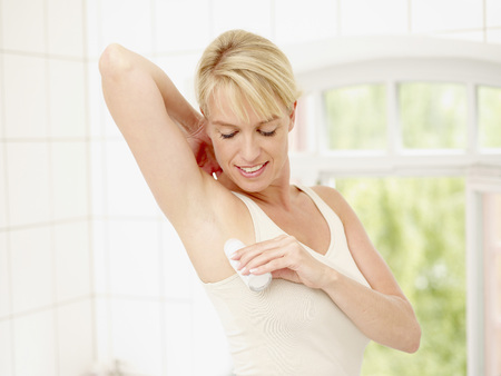 Mature Woman Putting Deodorant On Underarms,Smiling