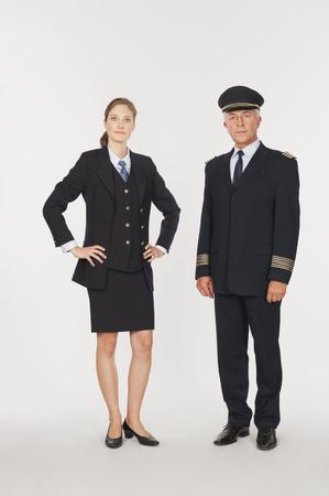 Capitán mayor y azafata de aire joven contra el fondo blanco, retrato