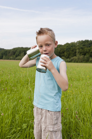 Germany,North Rhine-Westphalia,Hennef,Boy Standing In Meadow And Playing With Tin Can Phone LANG_EVOIMAGES