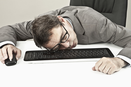 Close Up Of Mature Businessman Lying On Keyboard At Office