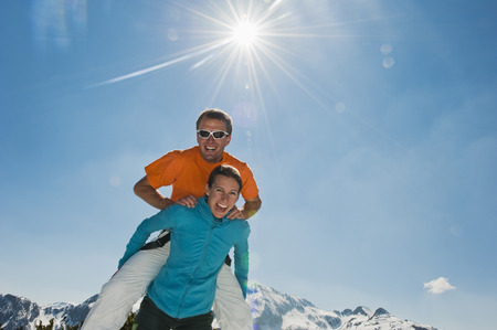 Austria,Salzburg Country,Altenmarkt-Zauchensee,Mid Adult Man Jumping Above Woman In Winter