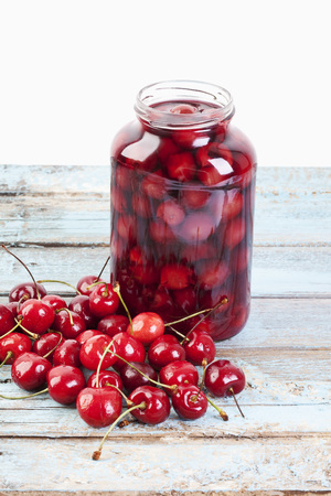 Cherries Beside Open Jar Of Cherry Compote On Wooden Table,Close Up LANG_EVOIMAGES